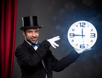 Magician performing a magic trick with clock Stock Photos