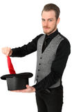 Magician performing. With a red handkerchief and top hat. Wearing a black shirt and vest. White background Stock Images