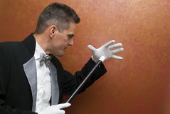 Magician performing with wand. Magician performing a magic trick Royalty Free Stock Images