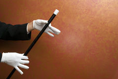 Magician performing with wand. Magician performing a magic trick Royalty Free Stock Photos