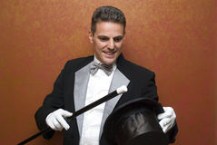 Magician performing with wand. Magician performing a magic trick Stock Image