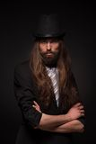 Magician. Portrait of handsome magician performing black magic. Long-haired bearded man with his arms crossed Stock Photography