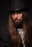 Magician. Portrait of handsome magician performing black magic. Man with long hair and top hat isolated on dark background Royalty Free Stock Images