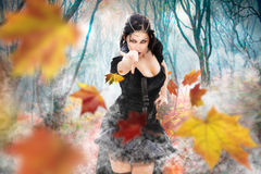 Magician witch power girl. Superpowers dark sorceress woman. Fall foliage forest. Witch. A beautiful sorceress queen with black suit unleashes her power Royalty Free Stock Photo