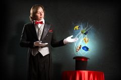 Magician. Produces a cylinder of magic and little fishes Royalty Free Stock Image