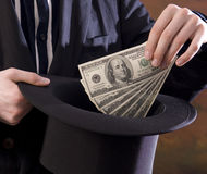 Magician pulling money from top hat Royalty Free Stock Photography