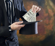 Magician pulling money from top hat Royalty Free Stock Image