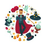 Magician in red cloak surrounded with equipent for tricks Royalty Free Stock Photo