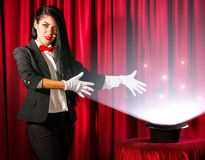 Magician showing to a hat with lights and fumes going out Royalty Free Stock Images