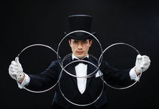 Magician showing trick with linking rings. Magic, performance, circus, show concept - magician in top hat showing trick with linking rings Stock Photos