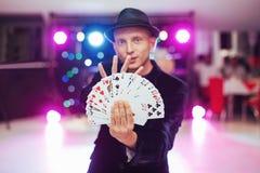 Magician showing trick with playing cards. Magic, circus Stock Photos