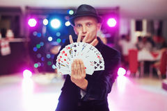 Magician showing trick with playing cards. Magic, circus Royalty Free Stock Photos