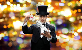 Magician showing trick with playing cards. Magic, gambling, casino, people and show concept - magician in top hat showing trick with playing cards over nigh Stock Photography