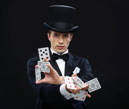 Magician showing trick with playing cards. Magic, performance, circus, gambling, casino, poker, show concept - magician in top hat showing trick with playing Stock Photography
