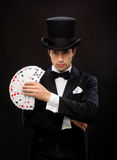Magician showing trick with playing cards Stock Image