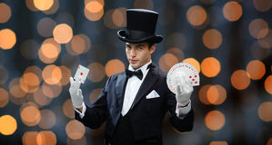 Magician showing trick with playing cards. Magic, performance, gambling, casino, people and show concept - magician in top hat showing trick with playing cards Stock Images