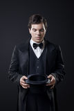 Magician showing tricks with top hat on dark Stock Images