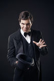 Magician showing tricks with top hat isolated. On dark background Stock Photography
