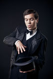 Magician showing tricks with top hat isolated. On dark background Royalty Free Stock Image