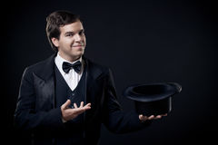Magician showing tricks with top hat isolated on dark Stock Photo