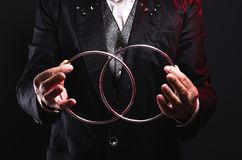 Magician shows trick with metal rings. Manipulation with props. Magician shows trick with metal rings. Sleight of hand. Manipulation with props stock images