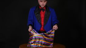 Magician shows trick with scarf and candle on dark background.  stock footage