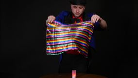 Magician shows trick with scarf and candle on dark background.  stock video footage