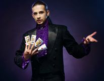 Magician in stage costume. Young brunette magician in stage costume showing card tricks royalty free stock image
