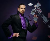 Magician in stage costume. Young brunette magician in stage costume showing card tricks stock photos