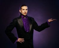 Magician in stage costume. Young handsome brunette magician in stage costume royalty free stock photos