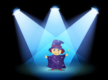 A magician standing at the stage with spotlights Royalty Free Stock Photos