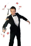 Magician with sword and cards. Young handsome magician pierce play cards with his sword during show isolated on white Royalty Free Stock Photos