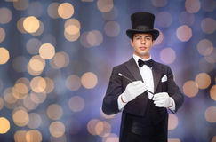 Magician in top hat with magic wand. Performance, circus, people and show concept - magician in top hat with magic wand over nigh lights background Stock Photo