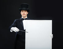 Magician in top hat with magic wand showing trick Royalty Free Stock Images