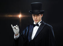 Magician in top hat with magic wand showing trick. Performance, circus, show concept - magician in top hat with magic wand showing trick stock image