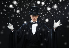 Magician in top hat with magic wand showing trick. Performance, circus, show concept - magician in top hat with magic wand showing trick stock photo