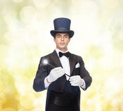 Magician in top hat with magic wand showing trick Royalty Free Stock Image