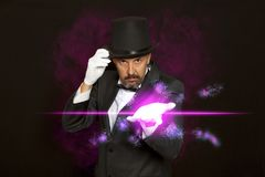 Magician in top hat showing trick on black stock photo