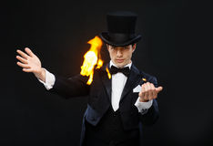 Magician in top hat showing trick with fire. Magic, performance, circus, show concept - magician in top hat showing trick with fire stock image
