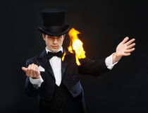 Magician in top hat showing trick with fire. Magic, performance, circus, show concept - magician in top hat showing trick with fire Royalty Free Stock Photo