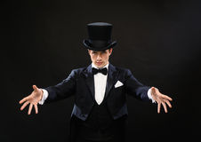 Magician in top hat showing trick. Magic, performance, circus, show concept - magician in top hat showing trick royalty free stock image