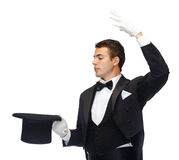 Magician in top hat showing trick. Magic, performance, circus, show concept - magician in top hat showing trick Stock Photos