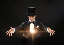 Magician in top hat showing trick. Magic, performance, circus, show concept - magician in top hat showing trick stock photo