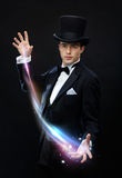 Magician in top hat showing trick. Magic, performance, circus, show concept - magician in top hat showing trick Royalty Free Stock Images