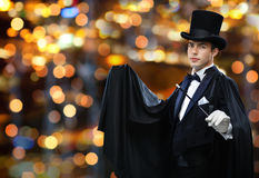 Magician in top hat showing trick with magic wand. Performance, circus, show concept - magician in top hat and cape showing trick with magic wand over nigh royalty free stock photos