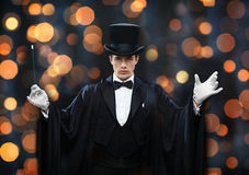 Magician in top hat showing trick with magic wand. Performance, circus, show concept - magician in top hat and cape showing trick with magic wand over nigh stock images