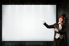 Magician in top hat and tie points to the banner Stock Photos