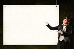 Magician in top hat and tie points to the banner Royalty Free Stock Photography