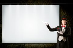 Magician in top hat and tie points to the banner Royalty Free Stock Image