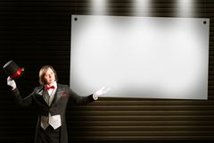 Magician in top hat and tie points to the banner Stock Images